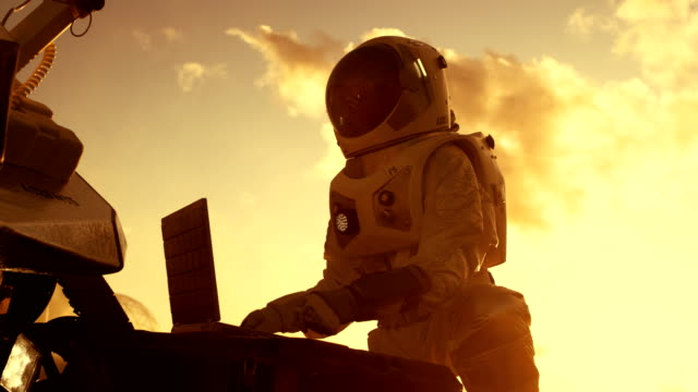 astronaut i rymddräkt verk på laptop, justera rover på en ny främmande röd planet, förmodligen mars. dagen ljus högteknologiska rymdutforskning, mission, att upptäcka och kolonisera beboeliga planeter. - mars bildbanksvideor och videomaterial från bakom kulisserna