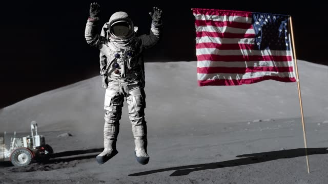 astronaut jumping on the moon and saluting the american flag. some elements of this video furnished by nasa. - księżyc filmów i materiałów b-roll