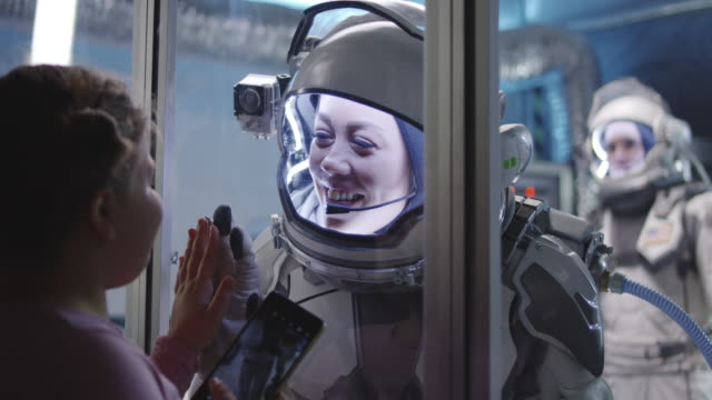 astronaut passende palme mit mädchen vor der abreise - raumanzug stock-videos und b-roll-filmmaterial