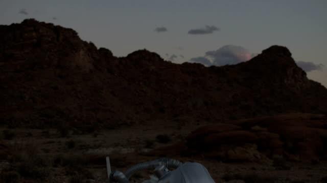 vídeos de stock, filmes e b-roll de astronauta em um planeta estranho descobre um estranho objeto metálico - amostra científica