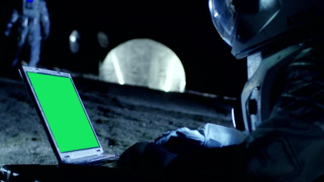 Astronauta del planeta extranjero trabaja en un portátil con pantalla verde de maqueta. En el fondo su miembro de la tripulación y los Habitat del espacio. Concepto de colonización extraterrestre. - vídeo