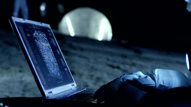 astronaut auf dem fremden planeten arbeitet mit ai-analyse auf einem laptop. im hintergrund ihrer crew-mitglied und lebendige station. kolonisation konzept. - raumanzug stock-videos und b-roll-filmmaterial