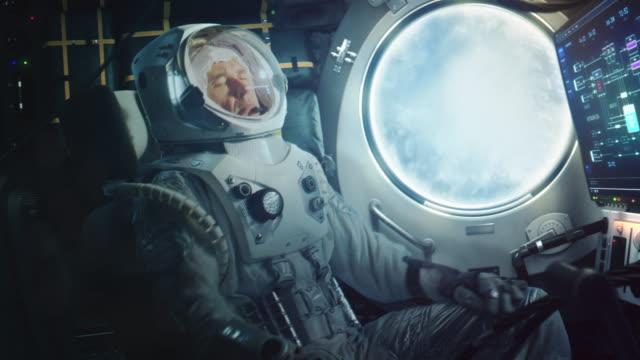 astronaut sitzt während des starts in einer weltraumrakete. erfolgreicher raketenstart schickt raumschiff ins all. kosmonaut erlebt g-kraft und vibrationen in der kapsel. wolken passieren in porthole. - rakete stock-videos und b-roll-filmmaterial
