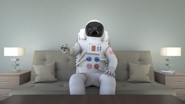 Astronauta, sentado en el sofá mientras ve televisión - vídeo