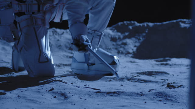 Astronaut using equipment to collect samples Medium close up shot of astronaut collecting and analyzing samples on Moon surface moon stock videos & royalty-free footage