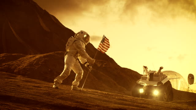 Astronaut Wearing Space Suit Plants American Flag on the Red Planet/ Mars. Patriotic and Proud Moment for the Whole of Humanity. Space Travel and Colonization Concept. video