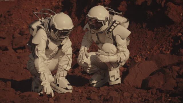 stockvideo's en b-roll-footage met astronauten die rotsmonsters verzamelen op mars - geologie
