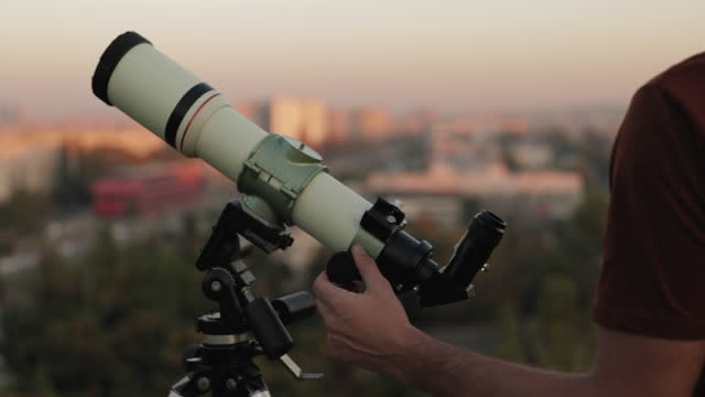 Astronomer with a telescope watching at the skies un urban surroundings.