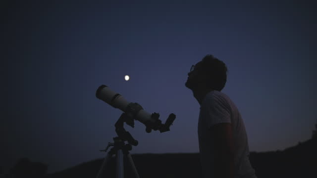 astronomer with a telescope watching at the stars and moon. - astronomia video stock e b–roll