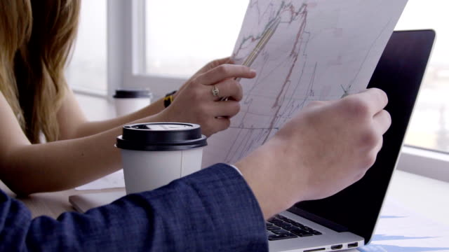 At desk woman with a pen in her hands shows the man a chart on paper video