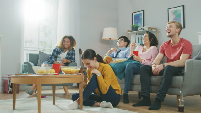 vídeos de stock e filmes b-roll de at home diverse group friends watching tv together, eating snacks and drinking beverage. they probably watching sports game, movie or sitcom tv show. young people having fun together. - equipamento desportivo