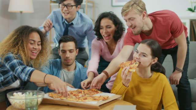 a casa diversi amici di gruppo che guardano la tv insieme, condividono pizza gigantesca, mangiando gustosi pezzi di torta. ragazzi e ragazze che guardano la sitcom comica o un film, ridendo e divertendosi insieme. - fetta video stock e b–roll
