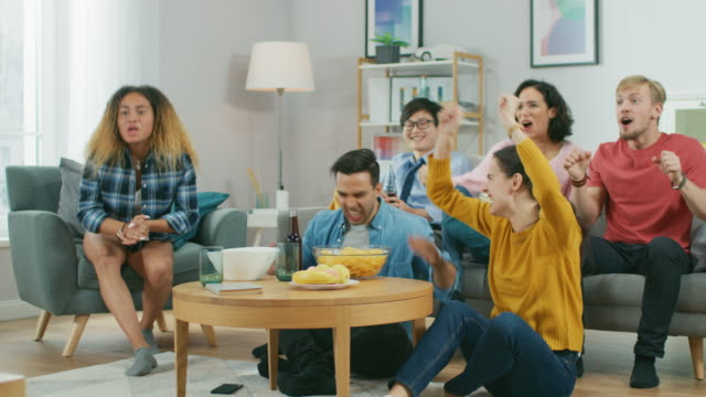 At Home Diverse Group of Sports Fans Sitting on a Couch Watching Important Sports Game Match on TV, They Cheer for the Team, Celebrate Victory after Team Scoring Winning Goal. Cozy Room with Snacks and Drinks.