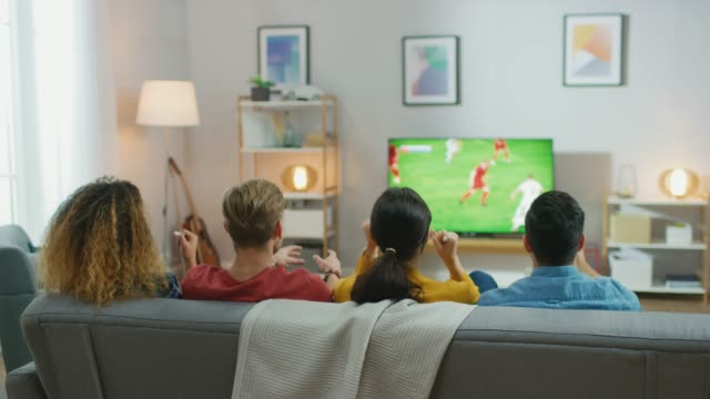 Video At Home Diverse Group of Sports Fans Sitting on a Couch Watching Important Soccer Match on TV, They Cheer for the Team, Celebrate Victory after Team Scoring Winning Goal. Cozy Room with Snacks and Drinks.