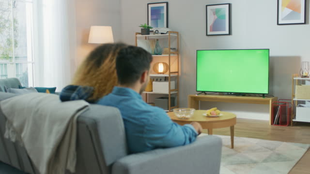 at home: girlfriend joins her boyfriend on a couch, they're watching green chroma key television screen. couple watching movies, tv shows, news. - oglądać filmów i materiałów b-roll