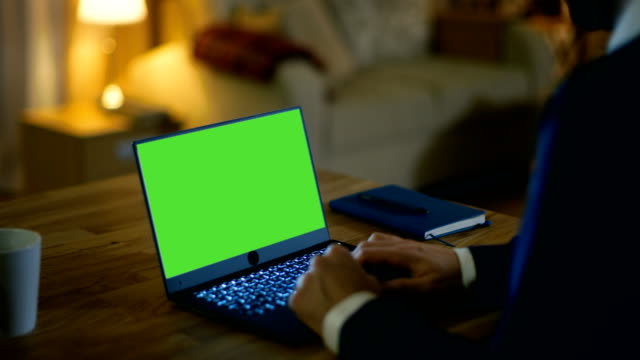 At Home Man Sits at His Desk and Types on a Laptop with Green Screen on It. His Apartment is Done in Yellow colours and is Warm. video