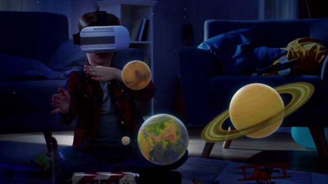At Night Before Going to Bed: Little Boy Wearing Augmented Reality Headset Plays with Space Learning Software, With Gestures He Manipulates 3D Planets, Discovers Facts About Solar System and Cosmos
