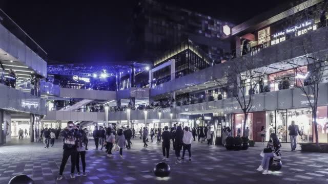 At night,walking among the fashion young people at the Sanlitun Village shopping square, Beijing, China video