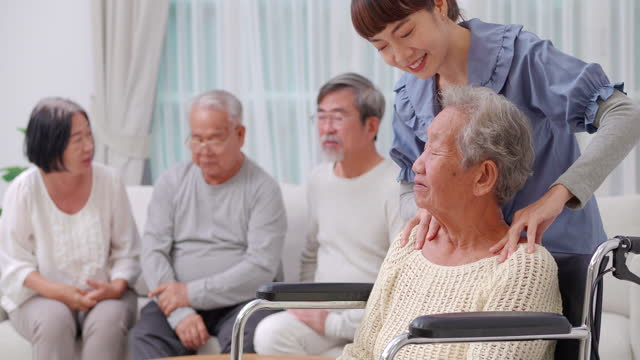 At Nursing home,Asian senior old woman sitting in wheelchair and talking to asian young female home caregive while her massage to shoulder of asian grandmother and nurses assisting elderly people at retirement home. video