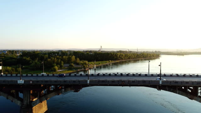 at sunset, the sun sets afternoon, areal view the long bridge over the river, cars come. in summer, among the space covered with green vegetation, cars move - lungo video stock e b–roll