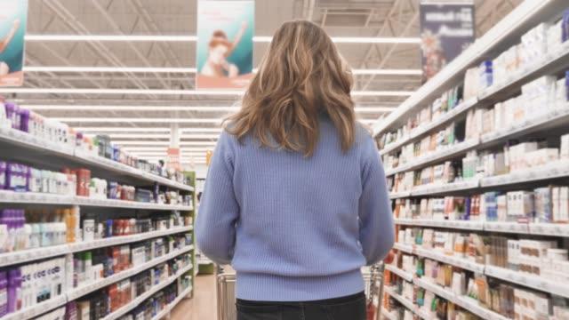 im supermarkt frau schieben einkaufswagen durch kosmetik-bereich des ladens - kosmetik stock-videos und b-roll-filmmaterial