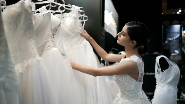 At The Bridal Salon Beautiful young woman searching for a wedding dress at the bridal salon. choice stock videos & royalty-free footage