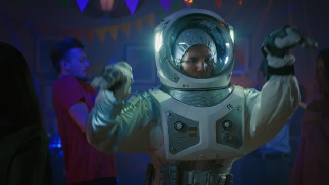 auf dem college haus kostümparty: lustige kerl trägt raumanzug tänze aus, groovy funky roboter moderne tanzschritte zu tun. mit ihm schöne mädchen und jungen tanzen in neonlicht. in zeitlupe. - raumanzug stock-videos und b-roll-filmmaterial