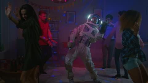 vídeos y material grabado en eventos de stock de en la fiesta de disfraces colegio casa: tío con traje espacial danzas apagado, haciendo movimientos modernos de baile robot funky groovy de la diversión. con él hermosas chicas y chicos bailando en luces de neón. en cámara lenta. - bailar