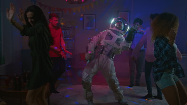 at the college house costume party: fun guy wearing space suit dances off, doing groovy funky robot dance modern moves. with him beautiful girls and boys dancing in neon lights. in slow motion. - zabawa filmów i materiałów b-roll