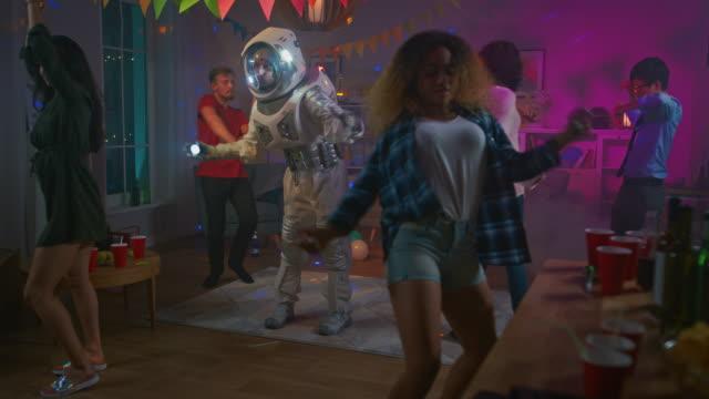 på college hus kostym festen: kul kille iklädd rymddräkt danser av, gör groovy funky robot moderna danssteg. med honom vackra flickor och pojkar dansa i neon lights. - nöjesklubb bildbanksvideor och videomaterial från bakom kulisserna