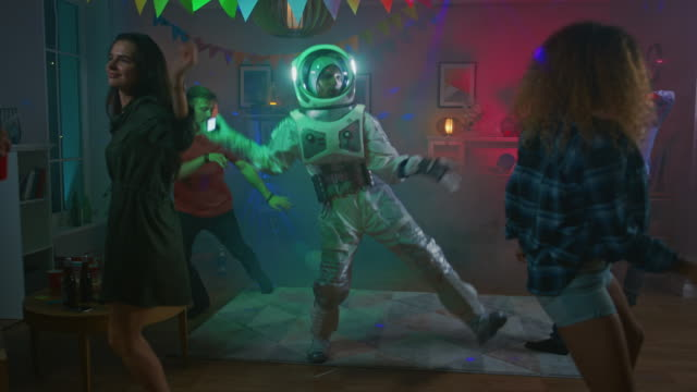 at the college house costume party: fun guy wearing space suit dances off, doing groovy funky robot dance modern moves. with him beautiful girls and boys dancing in neon lights. - struttura pubblica video stock e b–roll