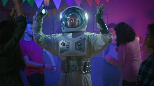 at the college house costume party: fun guy wearing space suit dances off, doing groovy funky robot dance modern moves. with him beautiful girls and boys dancing in neon lights. - attività del fine settimana video stock e b–roll