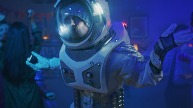 auf dem college haus kostümparty: lustige kerl trägt raumanzug tänze aus, groovy funky roboter moderne tanzschritte zu tun. mit ihm schöne mädchen und jungen tanzen in neonlicht. - raumanzug stock-videos und b-roll-filmmaterial