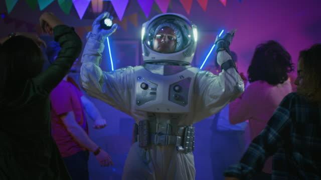 auf der college house costume party: fun guy wearing space suit dances off, doing funky dance moves. mit ihm schöne mädchen und jungen tanzen. stilvolle hand gezeichnet cartoon animation - spring break stock-videos und b-roll-filmmaterial