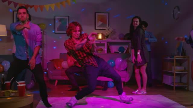 stockvideo's en b-roll-footage met op de college zaal verschijnende partij: diverse groep van vrienden hebben plezier, dansen en socialiseren. een man doet moderne dans moves, meisjes juichen. jongens en meisjes dansen in de cirkel. disco neon strobe lichten. - feest