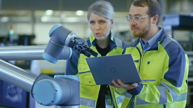 at the factory: female chief production engineer and  male automation engineer use laptop for programming robotic arm and discuss efficiency of the endeavour. new era in automatic manufacturing industry. - automatico video stock e b–roll
