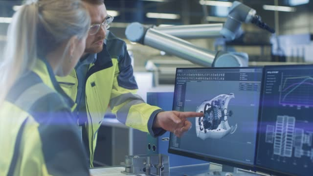 At the Factory: Male Mechanical Engineer and Female Chief Engineer Discuss Operational 3D CAD Designed Engine Prototype Shown on Screen. In the Background Futuristic factory with Automated Robotic Hands