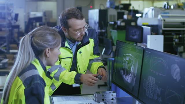Na fábrica: engenheiro mecânico masculino detém componente enquanto trabalho de engenheiro chefe fêmea no computador pessoal, eles discutir detalhes do Design do modelo 3D do motor. - vídeo