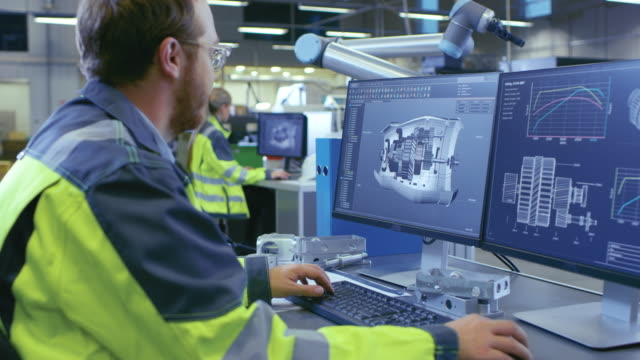 at the factory: mechanical engineer works on computer, designs in cad 3d model of the engine. in the background factory workers and functioning robotic arm. - azionare video stock e b–roll