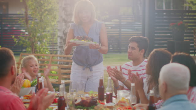 at the family garden party, mother brings dish with roasted bird to the table. family and friends gathered together at the big table. eating, drinking and having fun. - reunion stock videos & royalty-free footage