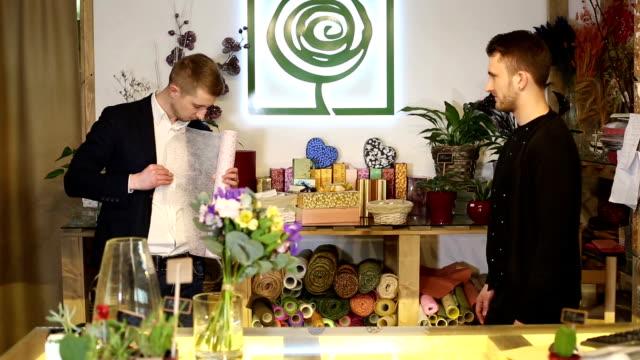 på blomsteraffär. två killar väljer dekorativa papper för inslagning en bukett blommor. - halmslöjd bildbanksvideor och videomaterial från bakom kulisserna