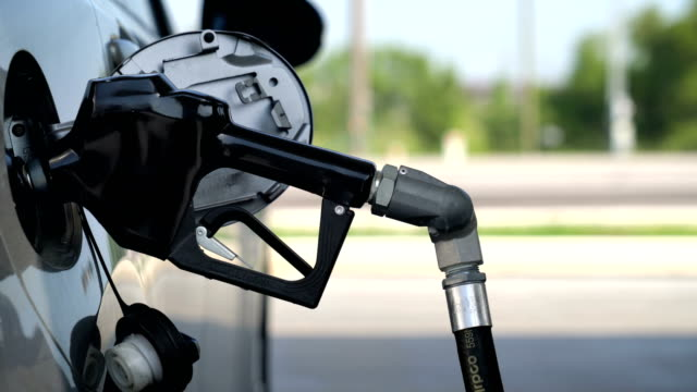 At the Gas Pump pumping gasoline as the gas pump or gas station in Texas  - focus on the gas pump handle refueling stock videos & royalty-free footage