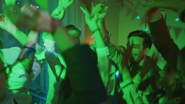 stockvideo's en b-roll-footage met op het feest van het huis: diverse groep van vrienden hebben plezier, dansen, springen, socialiseren. stijlvolle jongeren clubbing. disco neon lichten. in slow motion. - feest