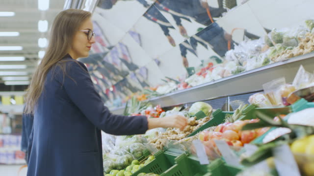 at the supermarket: beautiful young woman stands in the fresh produce section, chooses organic vegetables and fruits. customer shopping in the background. - bio food video stock e b–roll