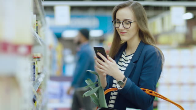 vídeos de stock e filmes b-roll de at the supermarket: beautiful young woman uses smartphone while browsing through the canned goods section of the store. she checks her shopping list and holds shopping basket. - online shopping