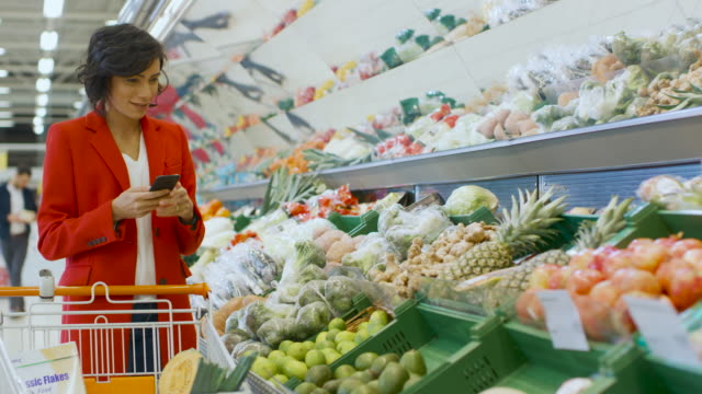 At the Supermarket: Beautiful Young Woman Walks Through Fresh Produce Section, Chooses Vegetables and Places them in Her Shopping Cart. Customer Uses Smartphone while Shopping for Fruits and Vegetables at the Store.