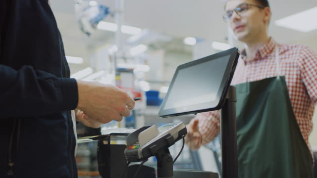 at the supermarket: checkout counter customer pays with smartphone for his  food items. big shopping mall with friendly cashier, small lines and modern wireless paying terminal system. - contactless payment stock videos & royalty-free footage