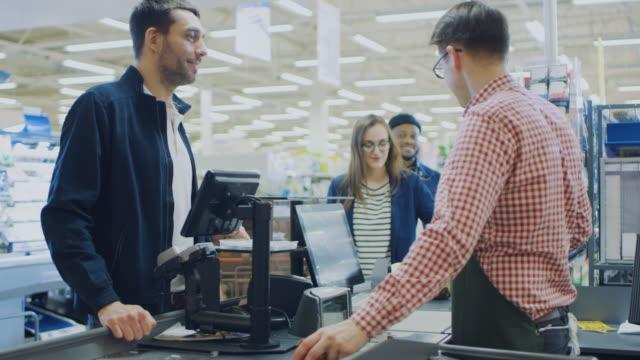 в супермаркете: выезд счетчик счастливый клиент чаты с дружелюбным кассиром, который сканирует свежие продукты и фрукты. современный торго - касса стоковые видео и кадры b-roll