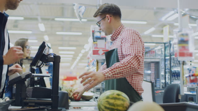 at the supermarket: checkout counter happy customer chats with friendly cashier who scans fresh groceries and fruits. modern  shopping mall with wireless paying terminal system. - video di credit card video stock e b–roll