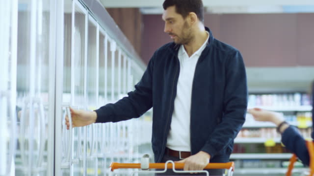 at the supermarket: handsome man opens freezer and places frozen items into shopping cart. man browsing through frozen goods section of the store. slow motion. - замороженные продукты стоковые видео и кадры b-roll